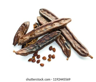 Carob. Healthy carob pods and seeds on white background