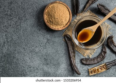 carob molasses in glass bowl and carob powder or flour with carob pods on rustic background, locust bean healthy food, Ceratonia siliqua ( harnup )