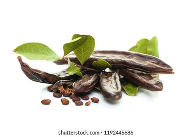 Carob on white background. Healthy organic sweet carob pods with seeds and leaves