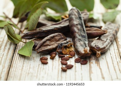 Carob on white wooden board. Healthy organic sweet carob pods with seeds and leaves. Healthy eating, food background.