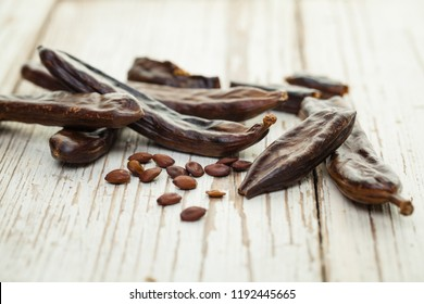 Carob pods. Healthy organic carob pods and seeds on white wooden table. Healthy eating, food background.