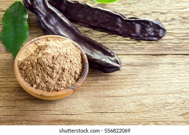 Carob pods and carob powder over wooden background with copy space - organic healthy ingredient for vegan vegetarian food and drinks