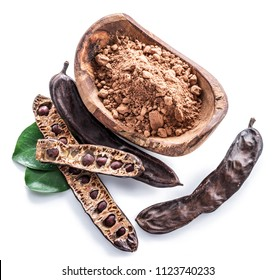 Carob pods and carob powder in the wooden bowl. White background.