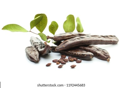 Carob pods, seeds and leaves on white. Healthy eating, food background.