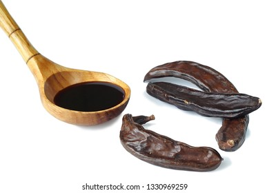 Carob pods and carob syrup in wooden spoon on the white background, close-up.