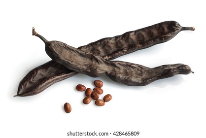 Carob podsand seeds isolated on a white background