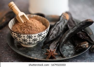 Carob powder and pods arranged