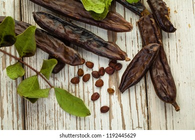 Carob top view. Healthy organic sweet carob pods with seeds and leaves on a wooden table. Healthy eating, food background.