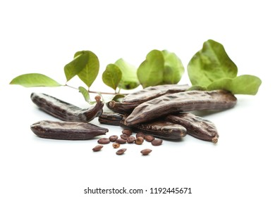Carob, white background. Organic carob pods with seeds and green leaves. Healthy eating, food background.