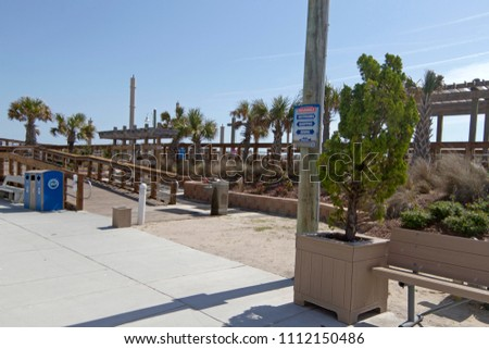 CAROLINA BEACH, NORTH CAROLINA - April 19, 2018: Carolina Beach Boardwalk on Pleasure Island, a tourist destination with benches, swings, shops, restaurants and bars and runs along the ocean and beach