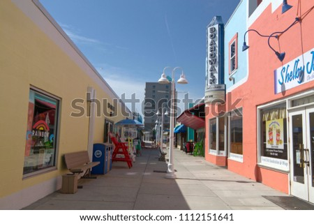 CAROLINA BEACH, NORTH CAROLINA - April 19, 2018: The colorful Carolina Beach Boardwalk on Pleasure Island, a tourist destination with shops, restaurants, bars, entertainment and a seaside boardwalk