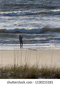 CAROLINA BEACH, NORTH CAROLINA, USA - APRIL 21, 2018: A man fly fishes in the sea from Carolina Beach