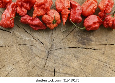 Carolina reaper extreme hot peppers on a wooden background arranged at the top with space for content on bottom.