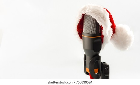 Carols and Merry Christmas music concept with a microphone wearing a santa hat isolated on white with copy space