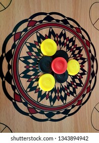 Carom board game with black, yellow and red pin (gacuk). Top view close up details.