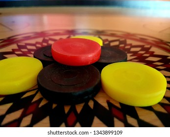 Carom board game with black, yellow and red pin (gacuk). Side view close up details.