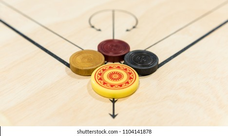 Carom board with striker, carom men, and queen, selective focus