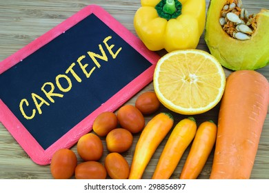 Carotene written on chalkboard with orange color fruits and vegetables