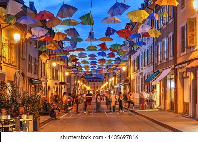Carouge, Geneva / Switzerland - June 23, 2019: Night scene in Carouge, Geneva, Switzerland along Rue Saint Joseph covered temporarly by colorful umbrellas. People queing for a popular ice cream shop.