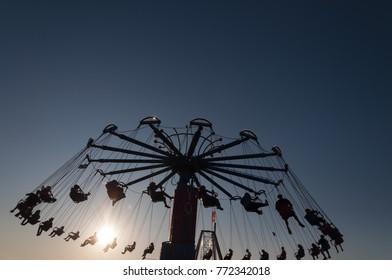 Carousel in amusement park, against dark blue sky