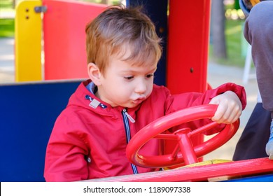 Carousel car in the amusement park for children. Boy playing on playground.