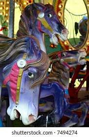 Carousel horses against the bright colors of the merry-go-round