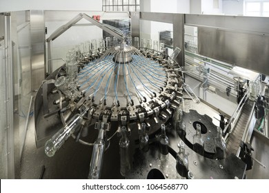 Carousel mechanism for the capture and turning of bottles, automatic machine for washing glass bottles. Factory for the production and bottling of spirits.