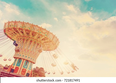 carousel ride spins fast in the air at sunset - vintage filter effects - a swinging carousel fair ride in amusement park at dusk