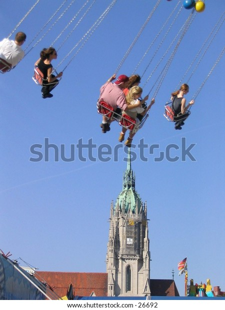 Carousell participants above a church steeple