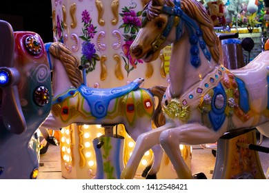 Carovigno/Brindisi, Italy - 08 09 2018: White horses with the blue saddle of a carousel for children during the fair in the city of Carovigno, in the south of Italy.