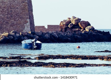 Carovigno/Brindisi, Italy - 08 08 2018: Holidays in the city of Carovigno, in the south of Italy. A solitary fishing boat on the Adriatic sea and in the background the old historic city castle.