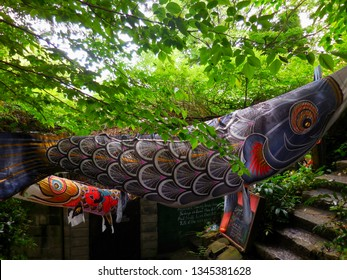 """Carp shaped streamers (banners) crossed at the old fashioned street in Hiroshima, Japan: translation """"Let's have a tea break with the beautiful Onomichi view"""""""
