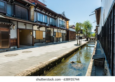 Carp swim in a stream running through a street with wooden houses in the old town of Furukawa in the Hida valley of Gifu Prefecture, Japan.