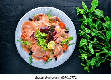 Carpaccio of fish, vegetables, cheese, spices, to Wooden background. Top view. Free space.