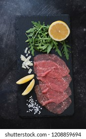 Carpaccio made of raw marbled beef and served with fresh rucola, lemon, parmesan and sea salt on a stone slate tray, top view, vertical shot