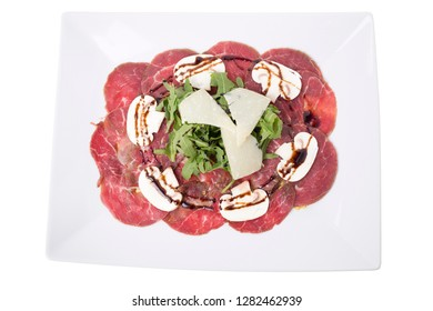 Carpaccio meat with parmesan cheese and arugula. It is isolated in a white background. CLose-up.