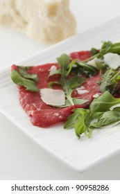 Carpaccio of raw meat, rocket and slices of cheese