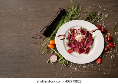 carpaccio with vegetables on a wooden table