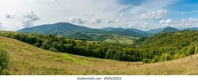 carpathian countryside in september. beautiful mountain landscape with grassy field on the hill. rural scenery with village in the distant valley on a sunny day with clouds on the sky