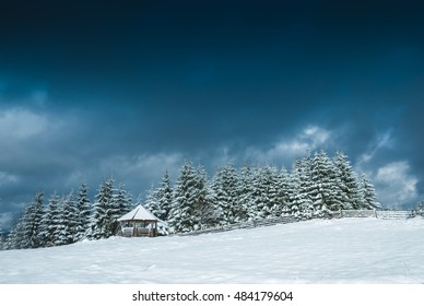 Carpathian mountain village covered by fresh snow with dark low dramatic snowy clouds in a sky. Ukraine, Europe