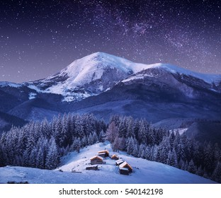 Carpathian mountain village in light of rising moon with wooden houses on a hill covered with fresh snow. Fantastic milky way in a starry sky. Christmas winter night.