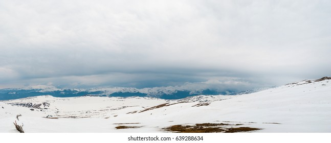 Carpathian mountains covered in snow and heavy clouds panoramic view in winter.