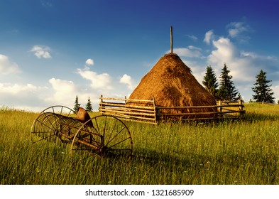 Carpathian mountains summer landscape with blue sky, clouds, haystack and old rusty agricultural instrument, natural summer background