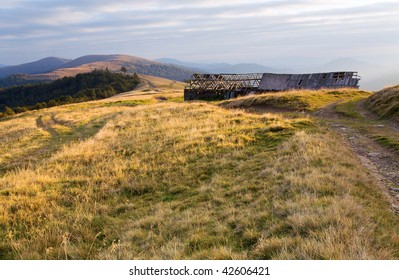 Carpathian Mountains (Ukraine) autumn landscape with cattle-breeding farm and country road.