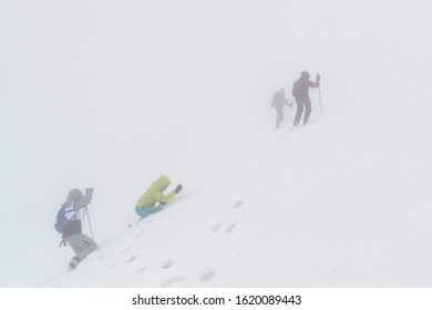 CARPATHIAN MOUNTAINS / UKRAINE – MARCH 9 2019: Female climbers trying to reach the summit in extreme bad weather in winter