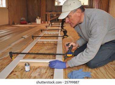 Carpenter adjusting clamp on exterior trim assembly