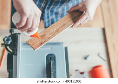 Carpenter applied glue on wooden board in his workshop. Selective focus and small depth of field.