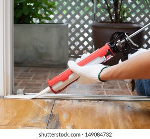 Carpenter applies silicone caulk on the wooden floor for sealant waterproof