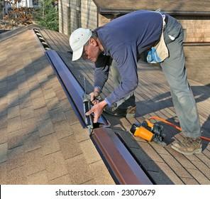 Carpenter applying caulk to ridge vent