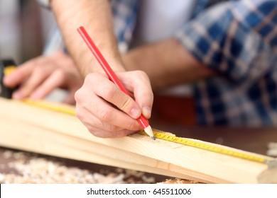 Carpenter applying marking onto wooden board in workshop, closeup